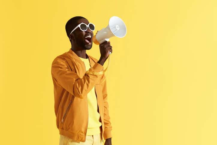 Man in yellow with yellow background shouting into megaphone