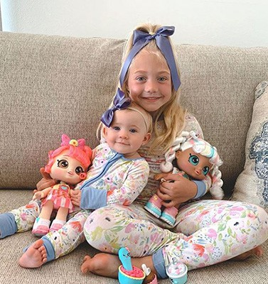 Kid Influencer with baby and dolls on sofa