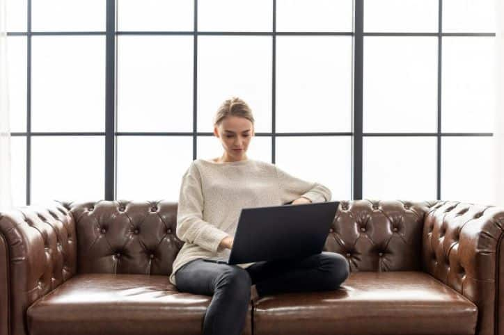 Woman sitting on leather sofa working from home on laptop   Influencer Marketing Changes in 2020